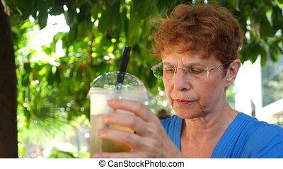 Lovely elderly woman is walking in the city park. She drinks...