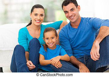 lovely family at home - lovely young family of three sitting...