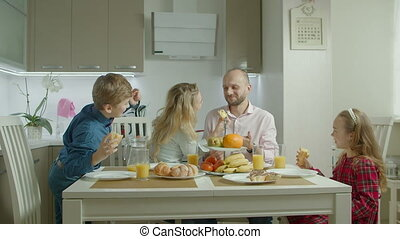 Lovely family enjoying meal in domestic kitchen - Happy...