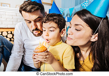 Lovely family making a wish while blowing out candle