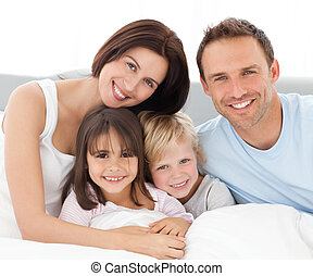 Lovely family sitting together on the bed in pyjamas