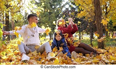 Lovely family throws dry yellow leaves in sunny autumn park...