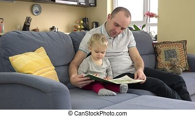 Lovely father reading story book with his baby at home.
