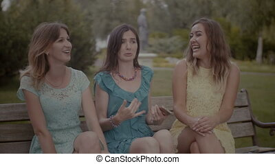 Lovely female friends gossiping on the bench - Happy...