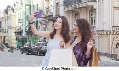 Lovely female friends taking selfies on smart phone after shopping. Two beautiful female friends having fun in the city, taking selfies with shopping bags. Friendship, weekend concept