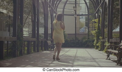 Lovely female taking a stroll in summer park - Stylish...