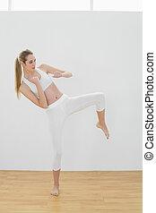 Lovely fit woman doing martial arts wearing sportswear
