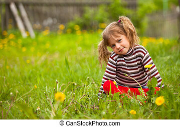 Lovely five-year girl sitting in grass.