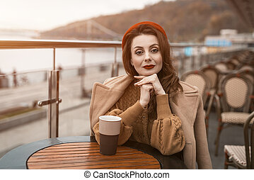 Lovely french young woman sitting at restaurant terrace with coffee mug looking at camera. Portrait of stylish young woman wearing autumn coat and red beret outdoors.