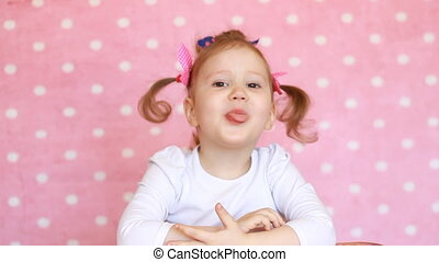Lovely funny girl child shows tongue, smiles and laughs