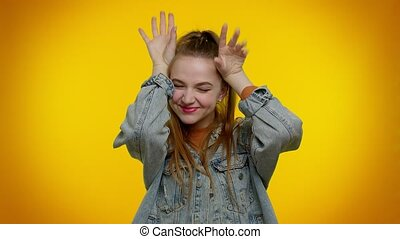 I am little bunny rabbit. Lovely funny teen girl 20s years old smiling friendly and doing bunny ears gesture on head, having fun, fooling with humorous comical mood. Young woman on yellow background