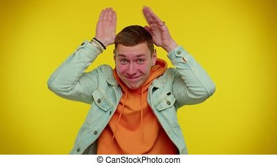 I am little bunny rabbit. Lovely funny teen boy 20s years old smiling friendly and doing bunny ears gesture on head, having fun, fooling with humorous comical mood. Young man on yellow background