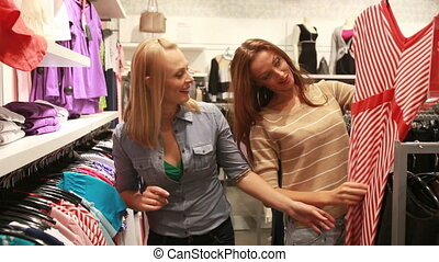 Lovely garments - Two girlfriends enjoying shopping trying...