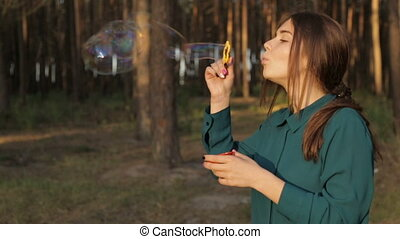 Lovely girl blowing soap bubbles