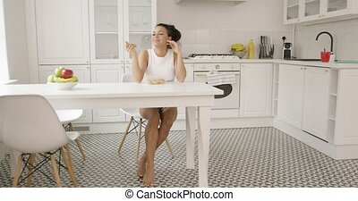 Lovely girl enjoying meal alone in kitchen