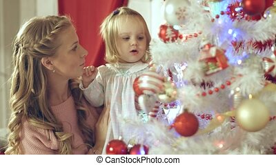 Lovely girl hangs christmas ball on the tree with her mother
