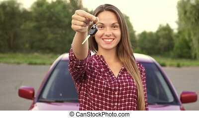 Lovely girl holding a key in her hand in a new car