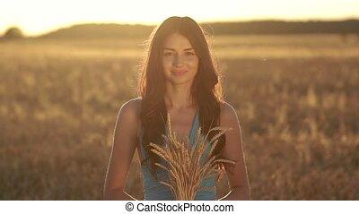 Lovely girl holding ripened wheat ears on field - Beautiful...