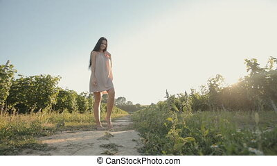 Lovely girl in a light airy dress posing in the vineyards in...
