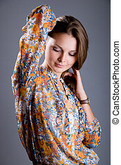 Lovely girl in a light colorful blouse on a gray background