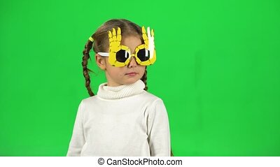 Lovely girl in funny glasses waving her head on green screen