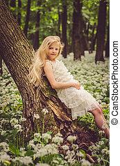 lovely girl in white dress in spring forest
