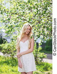 Lovely girl in white dress in summer, enjoying warm sunny day, beautiful blonde on nature