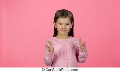 Lovely girl is clapping her hands on pink background -...
