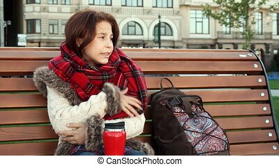 Lovely girl is feeling cold sitting on the bench