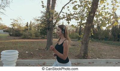 Lovely girl jogging through the park - Lovely girl jogging...