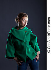 Lovely girl posing in trendy green coat, close-up