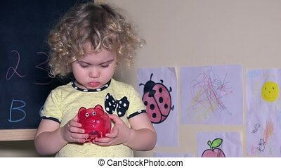 lovely girl shaking piggy bank with coins in it. Static...