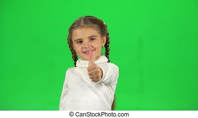 Lovely girl shows thumbs up like in studio on green screen