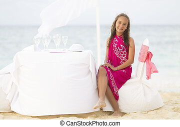 Lovely Girl Sitting at Table on the Beach