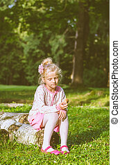 lovely girl sitting in tree trunk