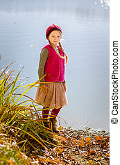 lovely girl standing by the pond