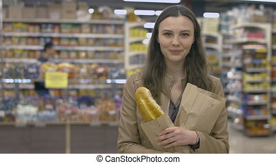 Lovely girl standing in the supermarket with a baguette in her hands