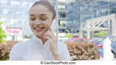 Lovely girl talking phone on urban background