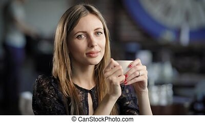 Lovely girl with coffee cup. Young beautiful female sitting in cafe with cup of coffee.