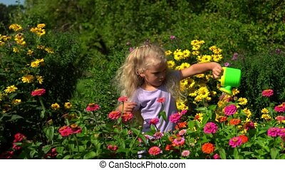 Lovely girl with plastic watering can waters flowers in summer garden