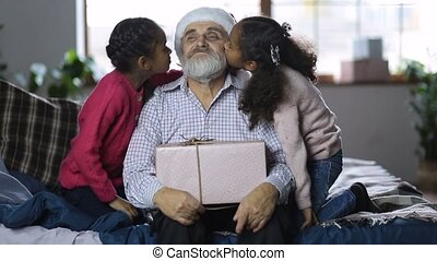 Lovely girls giving a kiss to grandpa at christmas