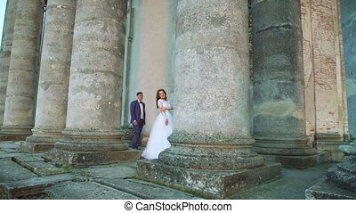 Lovely groom comes to bride and touches her near the castle. Slowly