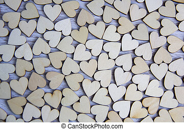 Lovely heart shape by wooden small hearts on rustic wood table. Love theme concept with wooden hearts for Valentine's day