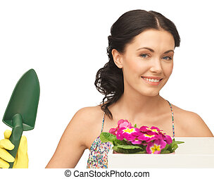 housewife with flower in box and gardening trowel