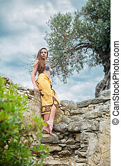 Lovely lady posing among antique ruins