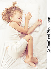 Lovely little boy lying in bed at home