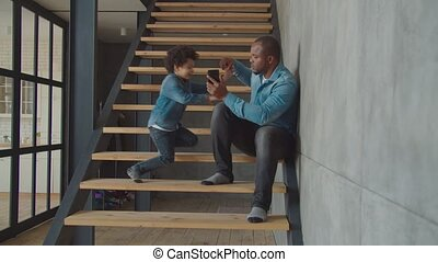 Lovely little boy talking on cellphone on stairs