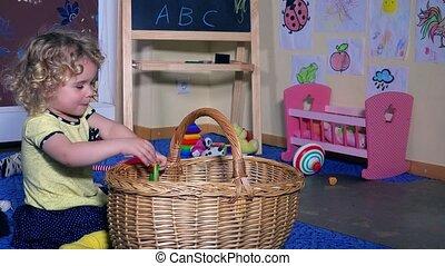 Lovely little girl child put all toys into wicker basket....