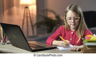 Lovely little girl e-learning with laptop at home