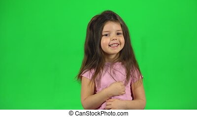 Lovely little girl is playing and make funny face on green screen